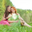 Funny mother and daughter sitting on green grass — Stock Photo #4713094