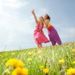 Funny mother and daughter on green grass — Stock Photo