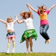 Happy Mother and two daughter jumping on green meadow - Stock Photo