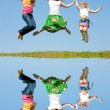Happy Mom and two daughter jumping on green meadow — Stock Photo