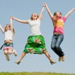 Happy Mother and two daughter jumping on green meadow — Stock Photo #4713259