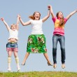 Happy Mother and two daughter jumping on green meadow — Stock Photo
