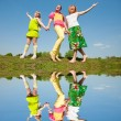 Stock Photo: Mother and two daughter jumping on green meadow