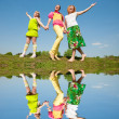 Mother and two daughter jumping on green meadow — Stock Photo