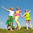 Mother and two daughter jumping on green meadow — Stock Photo #4713268