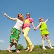 Mother and two daughter jumping on green meadow — Stock Photo #4713269