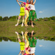 Mother and two daughter jumping on green meadow — Stock Photo #4713273