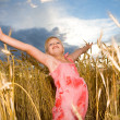 Little girl jumps in a wheat field — Stock Photo