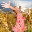 Little girl jumps in a wheat field. Against backdrop of cloudy s — Stock Photo