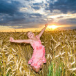Stock Photo: Little girl jumps in a wheat field. Against backdrop of cloudy s