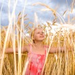Little girl in a wheat field. Against the backdrop of blue sky. — Stock Photo #4713300