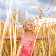 Little girl in a wheat field. Against the backdrop of blue sky. — Stock Photo