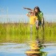 Stock Photo: Happy mother and daughter on field. Reflected in Water.