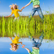 Happy woman and girl making exercises on field. — Stock Photo #4713340