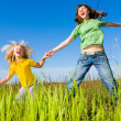 Happy woman and girl making exercises on field. — Stock Photo