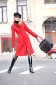 Girl in a red coat moves outdoors — Zdjęcie stockowe