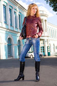 Beautiful Young Woman in jacket, blue jeans end boots. Against t — Stock Photo