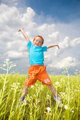 Happy boy jumping the field — Foto Stock