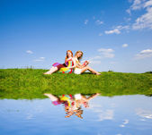 Two beautiful girls with notebook outdoors. Sitting on the green — Stock Photo