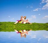 Две красивые девушки с ноутбука на открытом воздухе. Сидя на зеленый — Стоковое фото