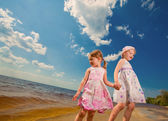Two cute sisters play in waves on sea — Stock Photo