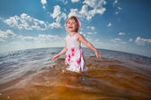 Cute girls play in the waves on sea — Stock Photo