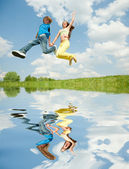Girl and boy jumping. Reflected in Water — Stock Photo