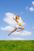 Happy young woman is dancing in a field — Stock Photo