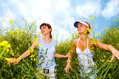 Two beautiful girl in white clothes go to the yellow flowers — Stock Photo