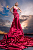 Beautiful girl in a long red dress holds an exotic flower in a h — Stock Photo