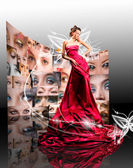 Beautiful girl in red dress against fantasy butterfly luminous — Stock Photo