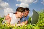 Happy couple on a laptop computer outdoors. Lay on the green gra — Stock Photo