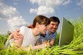 Casual happy couple on laptop computer outdoors. Lay on the gree — Stock Photo