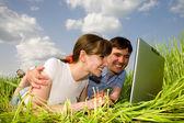 便携式计算机户外休闲快乐的夫妻。躺在格力 — 图库照片