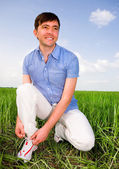 Man is Tying Laces In A Green Field — Stock Photo
