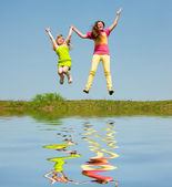 Two girls jumping on green meadow. Reflected in Water. — Stock Photo