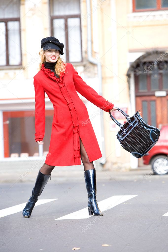 Girl in a red coat moves outdoors — Stock Photo #4710436
