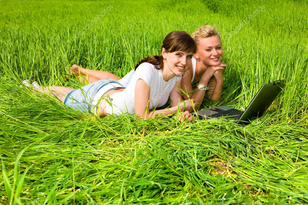 Two beautiful girls in white clothes are laughing near laptop computer outdoors. Lay on the green grass. — Stock Photo #4711941