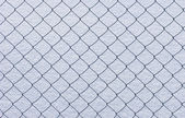 Wire netting on snow background — Stock Photo