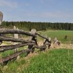 Old pole fence on outskirts — Stock Photo