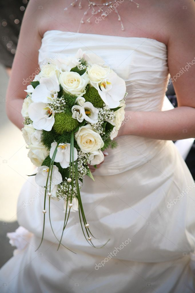 Bride is holding white wedding bouquet in her hand  Stock Photo #3577360
