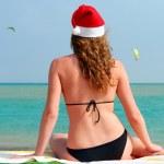 Beautiful woman in santa hat looking at sea — Stock Photo