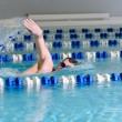 Man swims using the crawl stroke in indoor pool — Stock Photo