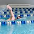 Man swims using the crawl stroke in indoor pool — Stock Photo