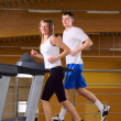 Stock Photo: Attractive couple is running on the treadmill