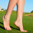 Beautiful female legs on grass near lake — Stock Photo #3203691