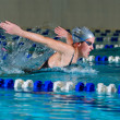 Woman swims using the butterfly stroke in indoor — Stock Photo #3203782