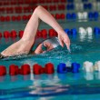 Woman swims using the crawl stroke in indoor poo - Stock Photo