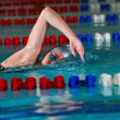 woman swims using the crawl stroke in indoor poo — Stock Photo