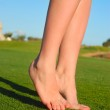 Beautiful female legs on grass near lake — Stock Photo